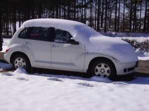 Car with layer of snow on it